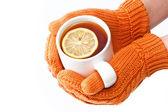 ruce v oranžových rukavicích, držící šálek čaje s citronem