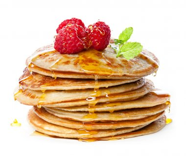 Small pancakes topped with honey, raspberries and mint