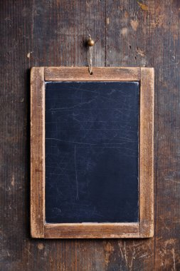 Vintage slate chalk board hanging on wooden background