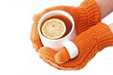 Hands in orange knitted mittens holding a cup of tea with lemon