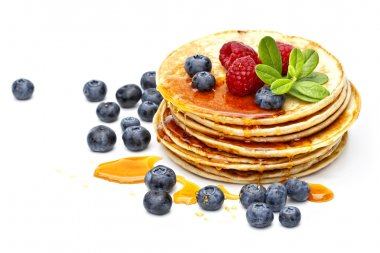 small pancakes topped with honey, raspberries and bilberries