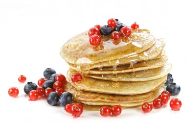 Small pancakes topped with honey, red currants and bilberries