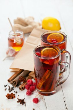 Cup of Hot winter raspberry tea with cinnamon sticks