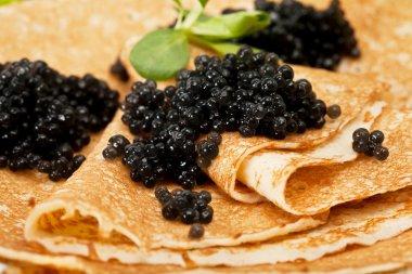 Pancakes with black caviar and greens