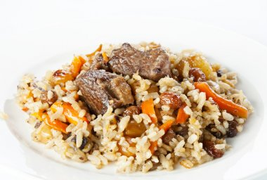 Uzbek national dish pilaf on white plate