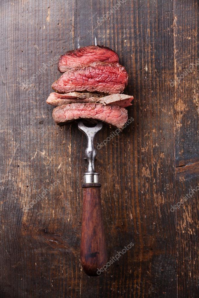 Slices of beef steak on fork