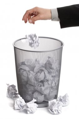 Hand dropping paper into wastepaper bin