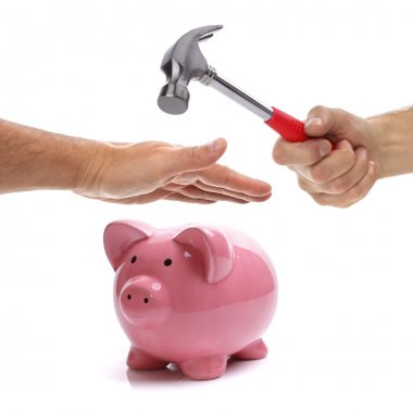 Hand with hammer about to smash piggy bank