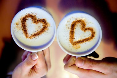 Goodmorning cup of coffee. 2 cups of coffee in hand and hearts are drawn on coffee foam.