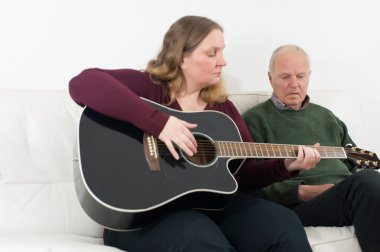 Young woman with guitar and pensioners