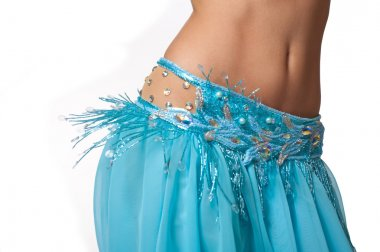 Close up shot of a belly dancer wearing a light blue costume shaking her hips.