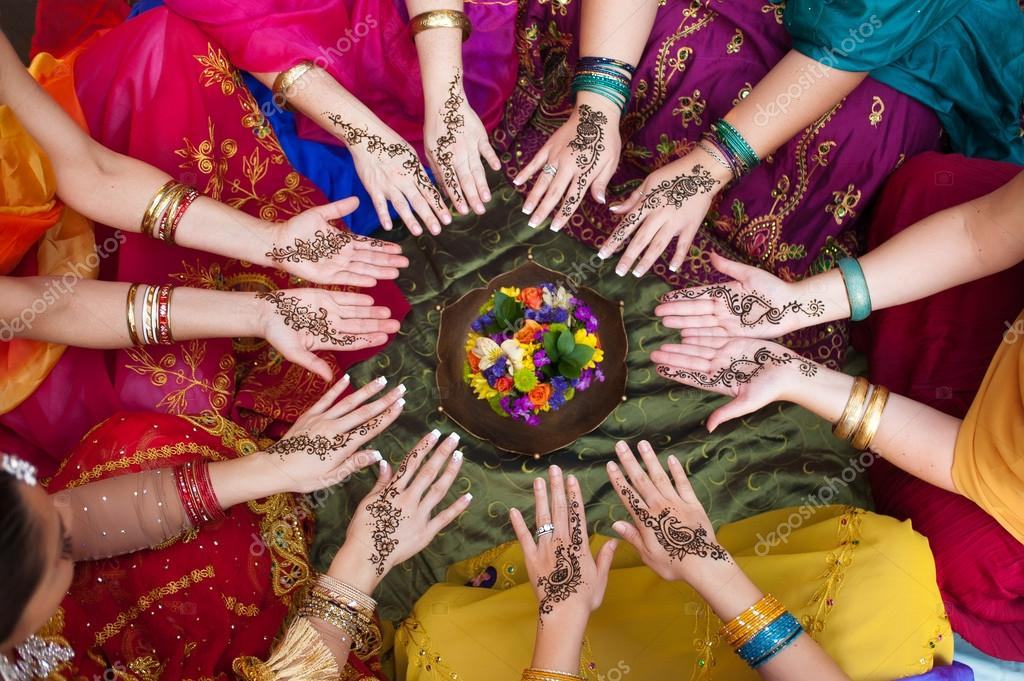 Six pairs of henna decorated female hands arranged in a circle