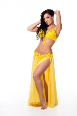 Full length photo of a beautiful belly dancer wearing a bright yellow costume.