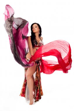 A beautiful bellydancer dances with two colorful, flowing, silk veils