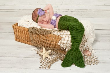 Newborn Baby Girl Wearing a Mermaid Costume Sleeping in Basket