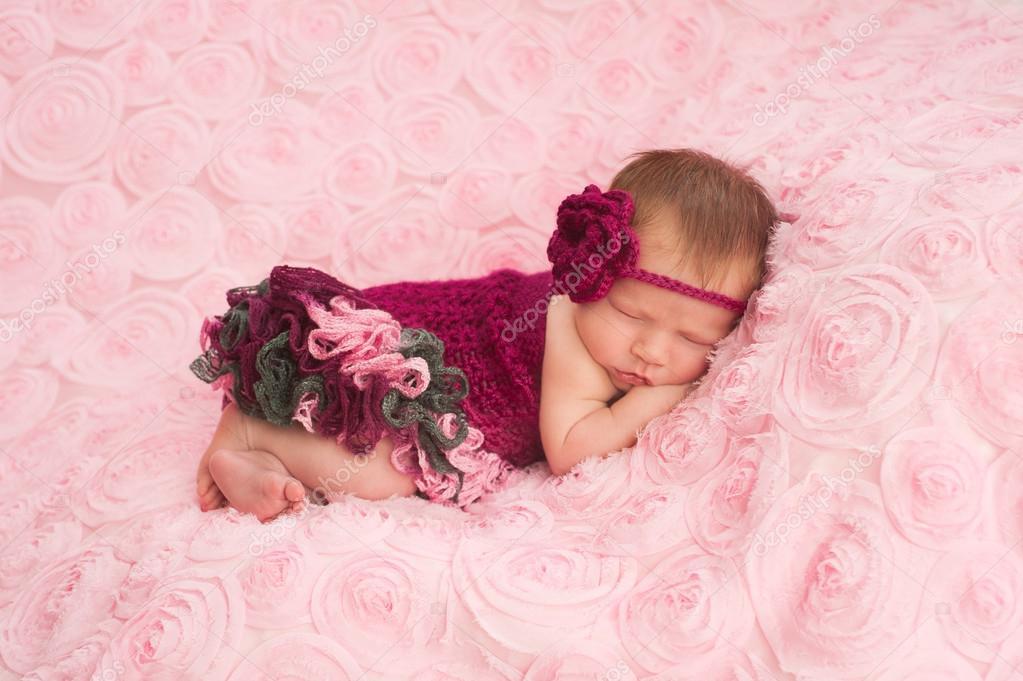453f0f1929 A sleeping newborn baby girl wearing a maroon crocheted headband and  romper.– stock image