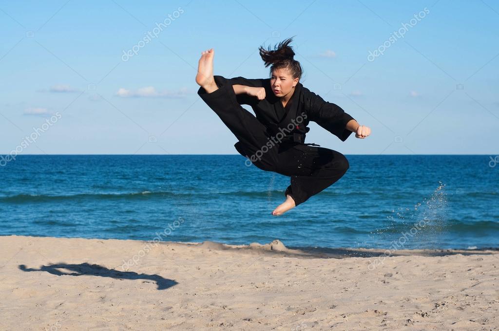 Female, fourth degree, Taekwondo black belt athlete performs a midair jumping kick on the beach.