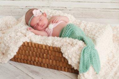 Newborn girl wearing a crocheted mermaid costume, sleeping in a basket