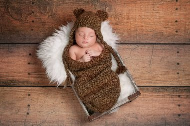 Newborn baby boy wearing a brown crocheted bear hat and sleeping in a vintage wooden box.