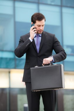 businessman talking at the phone and looking at watch