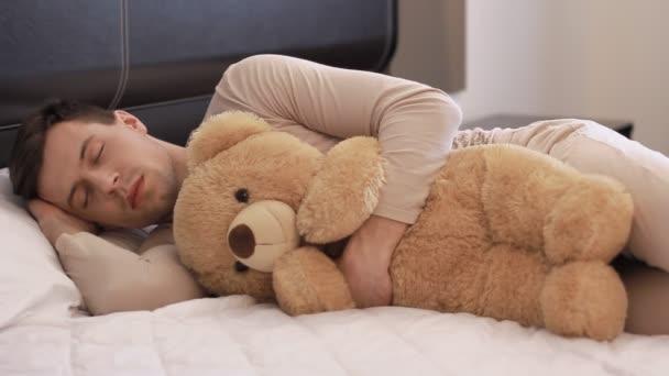 Guy is sleeping with teddy bear