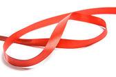lesklá červená saténová stuha na bílém pozadí