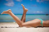 Fotografie Womens beautiful legs on the beach
