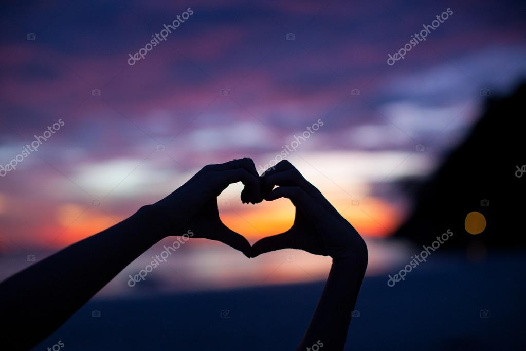 Silhouette hand in heart shape with sunset in the middle and beach background