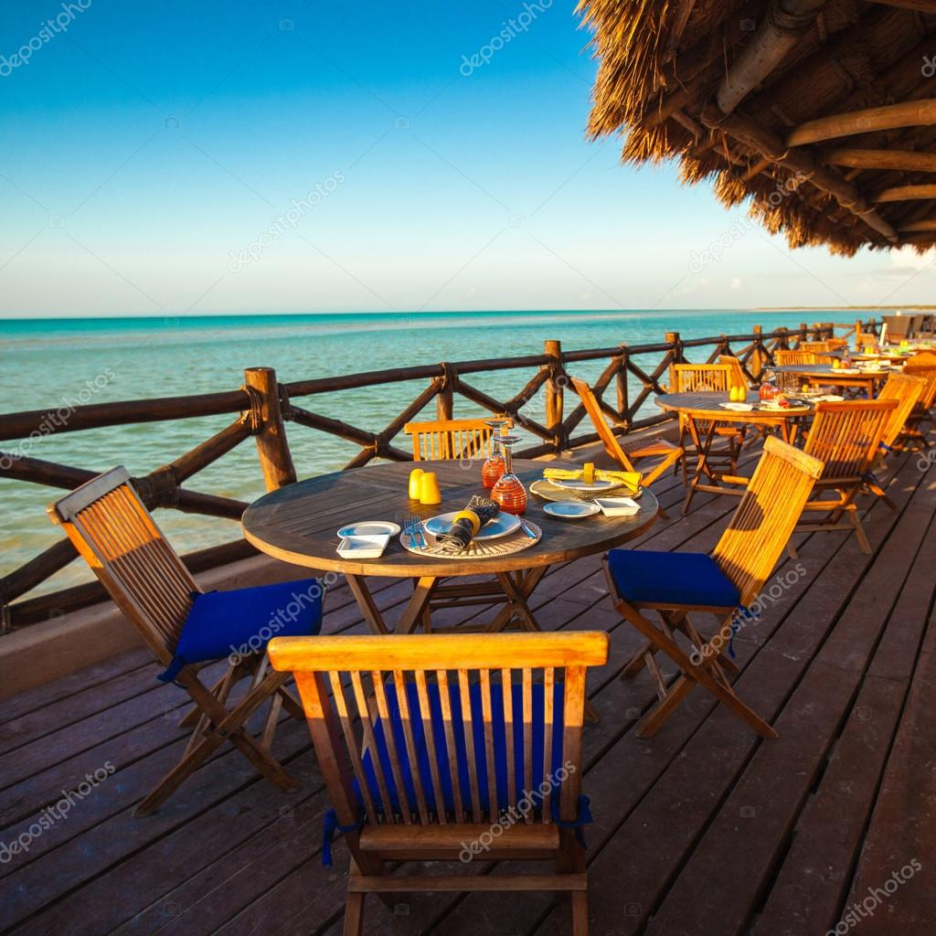Summer empty open air restaraunt near sea at sunset