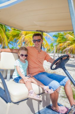 Golf cart with father and his little daughters inside at tropical country