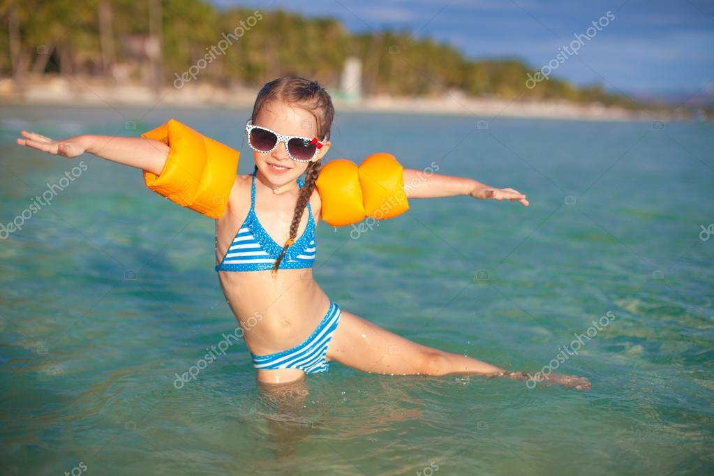 Adorable little girl have fun in the sea on tropical beach vacation