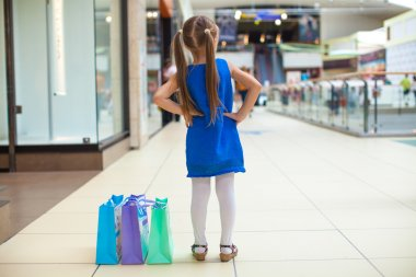Back view of fashion girl with packages in shopping center
