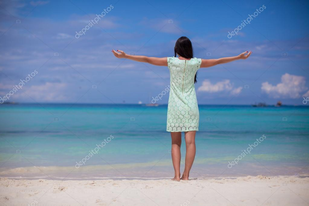 Back view of beautiful girl in dress walking like a bird on the beach