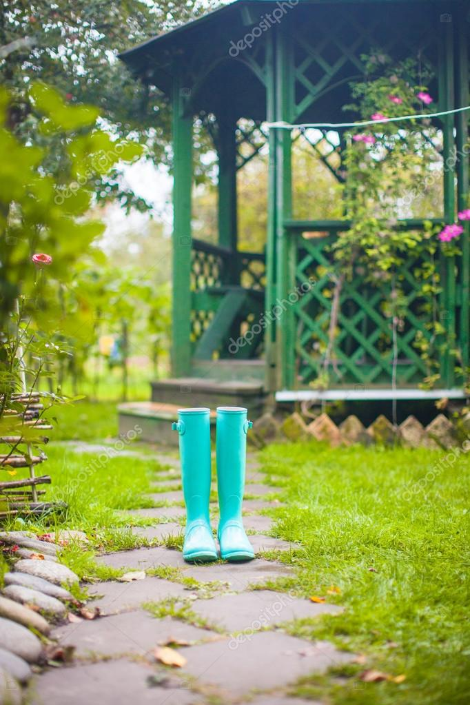 Bright fashionable rubber boots in the garden background of wooden pergolas