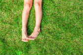 Közeli kép a két lábát egy fiatal lány, a fű a pázsiton