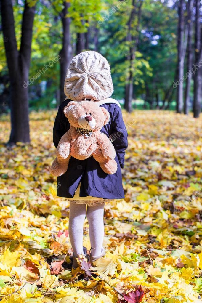 vue arri re de la charmante petite fille avec un sac dos ours derri re dans la for t d 39 automne. Black Bedroom Furniture Sets. Home Design Ideas