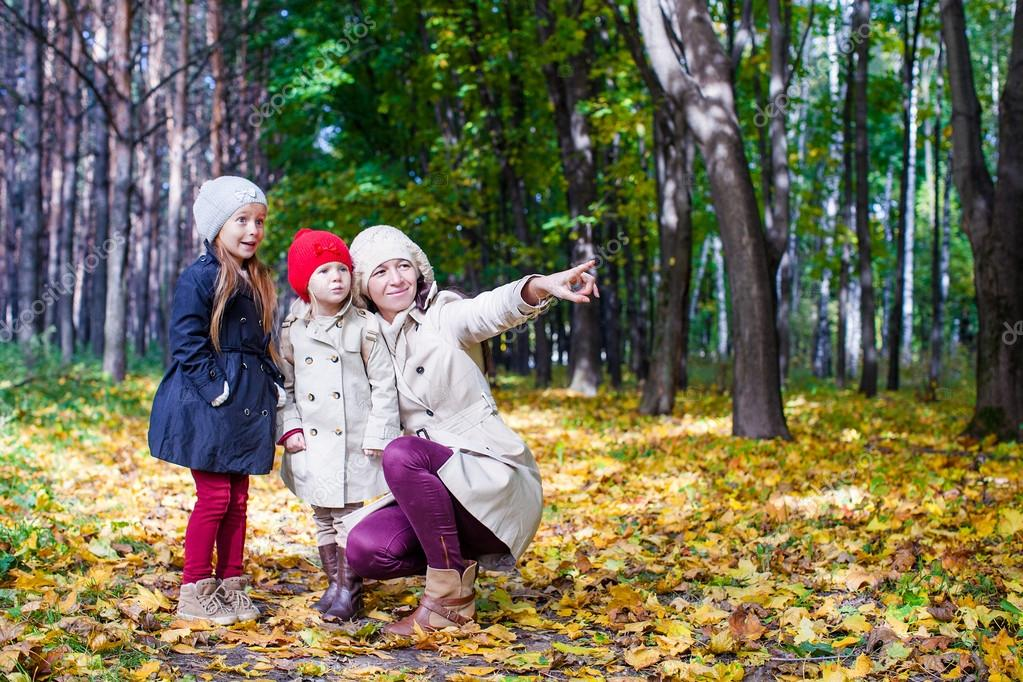 Young mother and her adorable daughter enjoying charming walk in yellow autumn forest on a warm sunny day