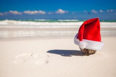 Santa Claus hat at coconut on a white sandy beach