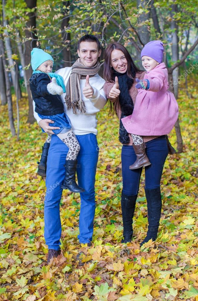 Family of four enjoying autumn vacation and showing a thumbs up