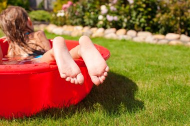 Close-up of a little girl's legs in small red pool