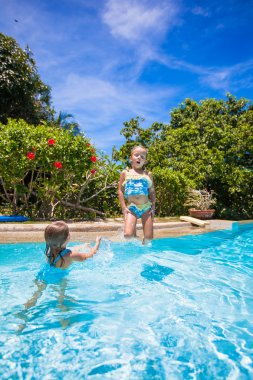Little girls jumping and having fun in swimming pool
