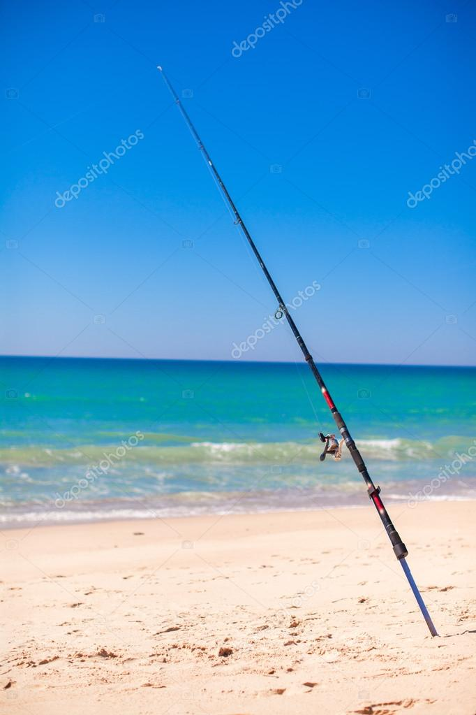 Fishing rod in white sand on tropical beach