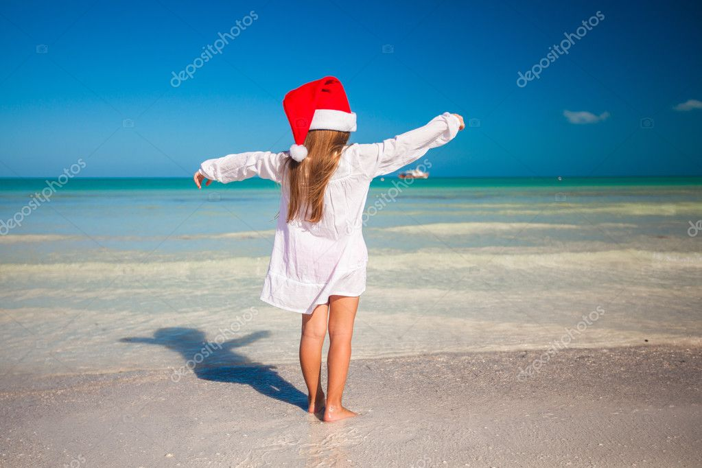 Back view of Little cute girl in red hat santa claus on the beach