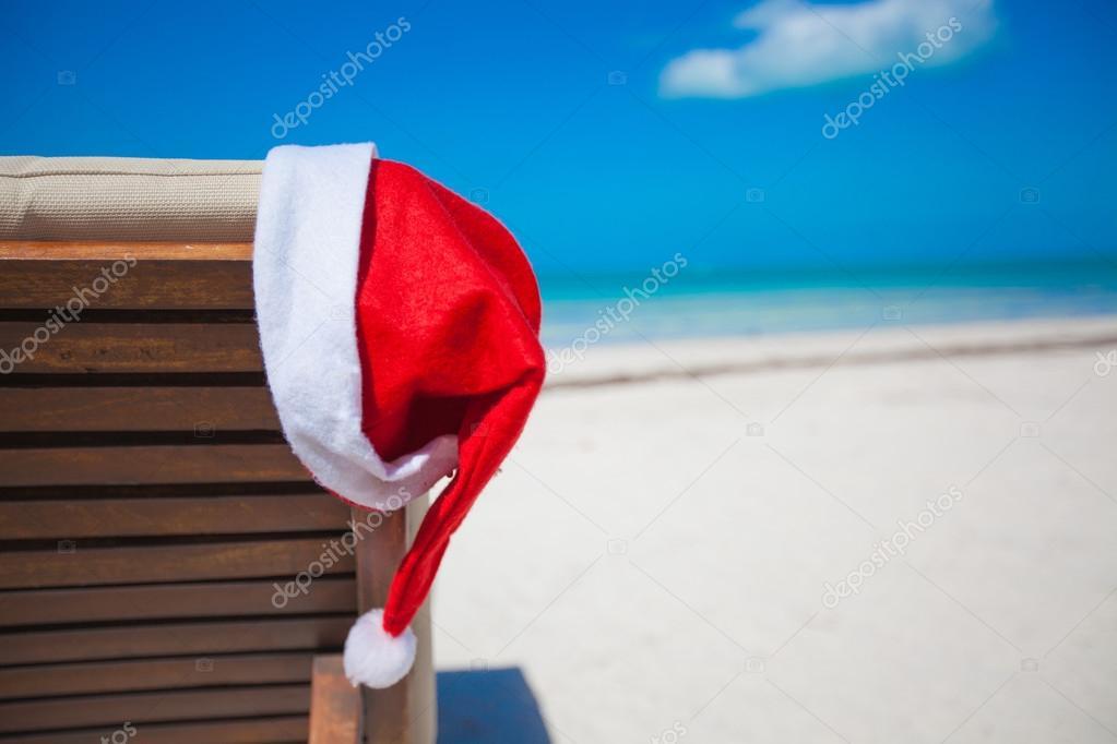 Close-up of santa hat on chair longue at tropical caribbean beach