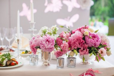 Beautiful bright bouquet of peony on the wedding table in vase