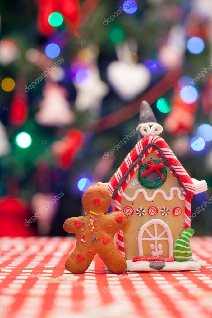 Gingerbread man in front of his candy ginger house background the Christmas tree lights