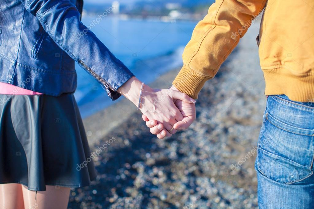 Rear view of a man and woman holding hands on the sea background