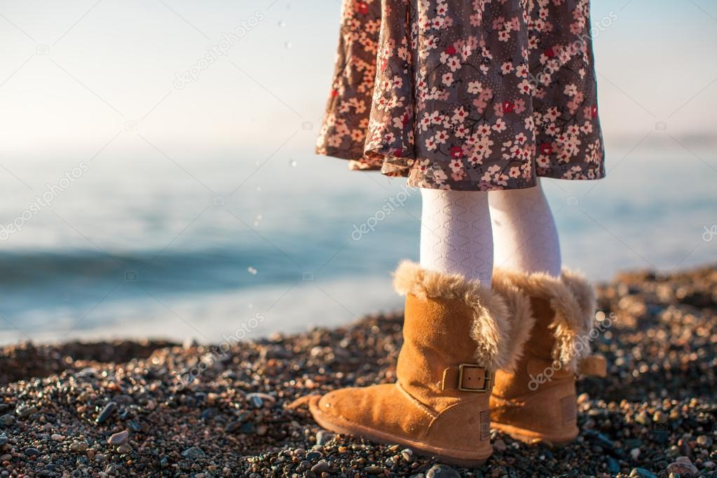 Closeup of legs little girl in cozy fur boots background the sea