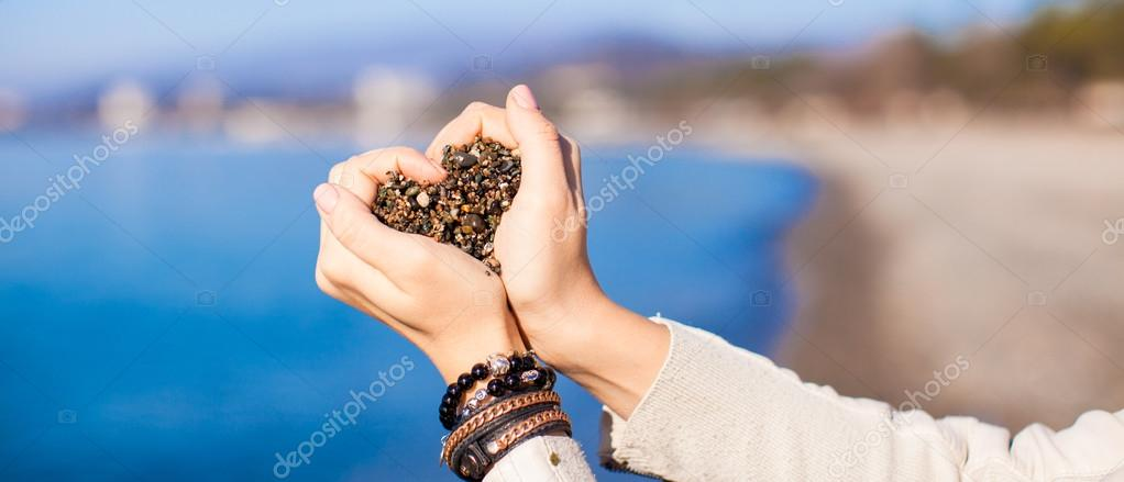 Woman hands forming heart shape background the sea
