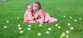 ältere Schwester küssen jünger auf einem grünen Lichtung von Ostereiern